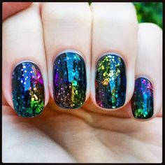 Stained glass nail look, created by painting nails black, adding a silver glitter polish, and then dabbing on different sheer colored polishes on top.