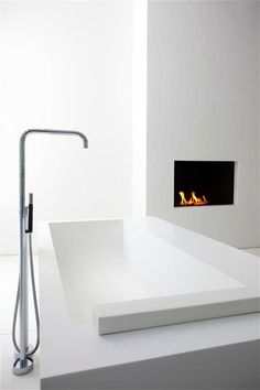 Bathroom with a fireplace, interior design by Sjartec Badkamers, bathub  by Antonio Lupi