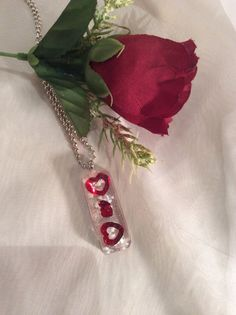This unique resin pendant is a Valentines celebration of bright red heart spangles, glitter and reclaimed glass shards. It comes on a ball chain and