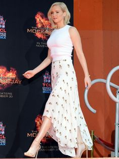 Jennifer Lawrence wears a white crop top, printed skirt, and Stuart Weitzman sandals