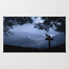 Down in the valley Area & Throw Rug A crow sitting on a cross looking down to the castle in the valley. Photomontage of some of my photos.   silhouettes, neo-mystical,blue, black, bird, dark, full moon, trees, nature, fog,landscape,nature,halloween,Berwartstein castle,mountains,cross