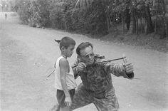 Een Public Relation man leert een Indonesische jongen om te gaan met een katapult. 1946. Indonesië, Nederlands-Indië