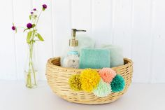 Upgrade a simple thrifted or outdated wicker basket this summer with a fun and flirty facade. Add a crafty touch with colorful oversized yarn pom poms on t