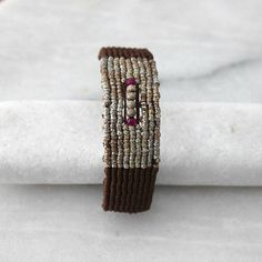 A chic macrame bracelet in brown and metallic colors to make your holiday arm party sparkly and modern! I made this bracelet with brown and metallic waxed cord, using micro macrame techniques. The braided section of the bracelet measures approximately 16 cm. It has a square knot
