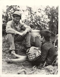 1944- U.S. 5th Army soldier chats with a small Italian boy during a lull in fighting at the Anzio beachhhead in Italy. Note the boy is holding his baby brother in his lap.