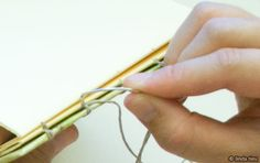 close-up tutorial of how to stitch the binding on coptic-stitched books