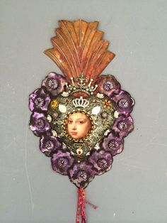 A large Mexican ( milagro) tin heart that is embedded with polymer clay, jewels, beads, and charms. Hand painted in silver and patina purple colors.