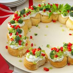2 tubs refrigerated crescent rolls  1 pkg. cream cheese, softened  1/2 c. sour cream  1 tsp. dill weed  1/8 tsp. garlic powder  11/2 c. broccoli florets  1 c. chopped celery  1/2 c. chopped red pepper  Cut each tube into 8 slices. Arrange 11-in. circle on ungreased 14-in. pizza pan. Bake at 375° for 15-20 mins. or until golden brown. Cool for 5 mins. cool completely. In a sm. bowl, beat the cream cheese, sour cream, dill & garlic powder smooth. Spread over wreath