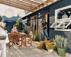 Dark grayish blue stucco walls and fence, white trim windows, wood beams, silver modern light  fixtures, drought-tolerant landscaping, paper lanterns hanging from patio cover.