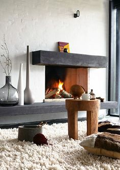 Fireplace. Everything on this picture is very cosy - coffee table, box for yarn, vases, soft carpet, colour combination...