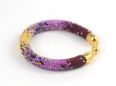 This Beaded Crocheted Bracelet is made of Japanese seed beads of superior quality with Swarovski Crystal - Lilac, Violet colors and 24K Gold . Incredible ruffle texture and sophisticated hue migration of romantic pastels, wildly tropical blends and powerful prime colors.  SIMPLY BEAUTIFUL Classic Bead Crochet Bracelet This Bracelet is one sweet, gentle friend . When you are having a bad day, it will fill you full of cheer!  BUSINESS OR PLEASURE. U will always say YES to this bracelet!  I am…