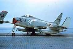 USN North American FJ-4 Fury From VF-151 Squadron, sits on the carrier deck with its wing folded.