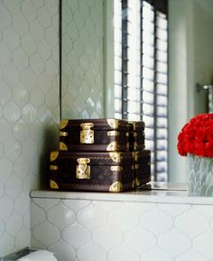 Louis Vuitton luggage being used as storage on a ledge in a tiled bath