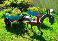 old tires, paint, a few screws, a weed wacker and imagination make this donkey pulling a cart of flowers