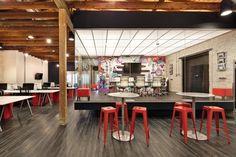 Mesinhas altas com banquetas para convivência e lanches rápidos - Inside Chaotic Moon Studios Austin Offices