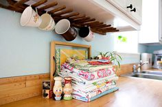 "Long Scrap of Wood + 1/2"" dowels + drill with 1/2"" bit + glue = under-cabinet coffee mug rack!"