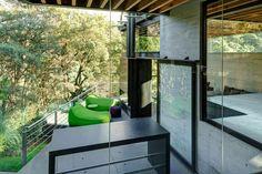 Lounge / Varanda com vista para o bosque, paredes de concreto, puff verde. Casa no bosque na Cidade do México por Grupoarquitectura