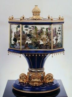 """Aquarium clock of 18 carat gold, lapis lazuli and rock crystal. Approx 24 inches in height. It is so designed that upon the hour or request the gemstone fish ( made of sculpted rubies emerald, tourmaline, aquamarine and citrine)and   undersea life """"swim"""" and scamper about their under sea world"""