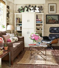 Exposed brick and a thrifted coffee table work together to create a rustic vibe in this room. Consider your living space as a place for your collections, too, like this homeowner's vintage fans. Click through for more design inspiration and living room decorating ideas.