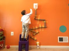 Make a wall marble run from cardboard tubes, painter's tape, and some other recycled trash. Click the video to see it in action!