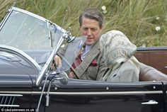 Hugh Grant cuts a dapper figure as he rides along in vintage car