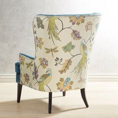 A graceful wing chair in search of a cozy corner, Asher is all about classic lines and mid-century modern legs. Upholstered in a gorgeous peacock blue, a lively print on the sides and the back, which features a beautiful peahen perched on a branch, it's ready to hold draped throws and stacked pillows. Why not invite a small table to hold tea and books?