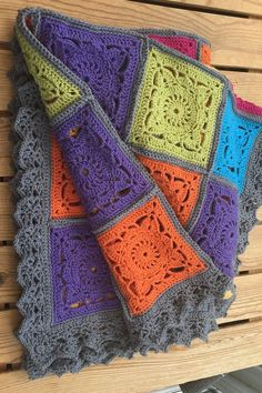 Beautiful, bright but not too bright rug/blanket/afghan/throw! Crocheted in acrylic yarn - which means it can be gently machine washed and dried flat and not too heavy to use easily. Each square has been chrocheted individually and then joined before a wide lace border has been added.