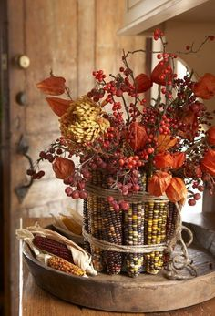 Art DiY Indian Corn Vase ::: Wrap a can with rubber bands. Then remove the husks from corn and simply slide the corn cobs in standing them upright. Cover the rubber bands with twine fill with fall flowers like dahlias, mums, berries and asters! holidays