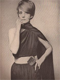 Jean Moreau in Cardin's sinuous aubergine short crepe evening dress, scarf-throated, cut asymmetrically to bare one shoulder.