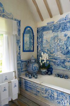 In a bathroom of an English manor house, a panel of circa-1730 Dutch scenic tiles decorates the wall above a Victorian tub. Beautiful!
