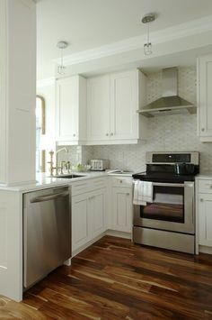 Sarah Richardson Design U shaped kitchen design with creamy white kitchen cabinets, beveled marble countertops and Saltillo Imports Marble Mosaics Long Octagon Tiles backsplash. Para Paints