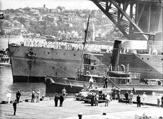 HMAS SYDNEY moored at East Circular Quay, February 10, 1941. . Text from ANMM: HMAS SYDNEY is seen mooring against the backdrop of the Sydney Harbour Bridge after returning from the Mediterranean Sea and service with the 7th Cruiser Squadron. Visible on S