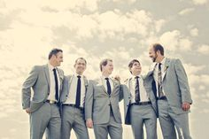 Grey suits, but with different blue ties, the groomsmen wear their jackets open with hands in pockets during the ceremony while groom's jacket is buttoned up. Love!