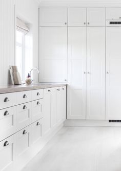 pure white kitchen. home decor and interior decorating ideas. wall of storage