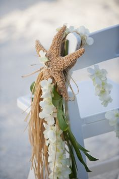 Wedding at the beach    use pine, for the largest strand.  Use white tulips, white orchids with stick and slate blue flowers as the front of the drappery.  Starfish on top and hook for seats.