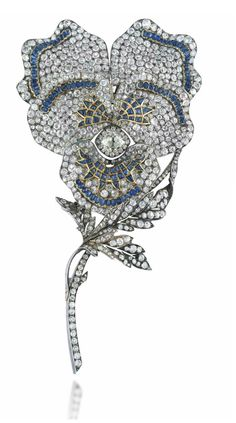 A LARGE LATE 19TH CENTURY SAPPHIRE AND DIAMOND BROOCH  Modelled as a pansy, the old-cut diamond centre to a pavé-set diamond five petal surround with buff-top and cabochon sapphire accents, raised on a diamond stem with curling leaf detail, mounted in silver and gold, circa 1890