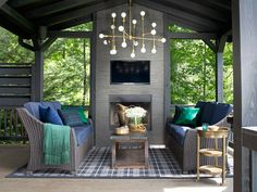 LOW COST LUXE The fireplace in this Georgia log cabin was covered in inexpensive porcelain tile. The brass chandelier finishes the space with a little sparkle.