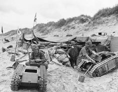 Members of the US Navy's Second Beach Battalion disassembling two German SdKfz 302 Goliath remote-controlled mines (a.k.a Beetles) on Utah Beach, 11 June 1944. http://wrhstol.com/2wreiTn