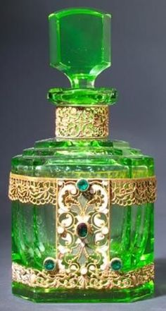 A perfume bottle, circa 1920s, in green crystal, with jeweled and enameled metalwork. Made Czechoslovakia
