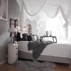 Biały baldachim i drewniane wezgłowie w sypialni