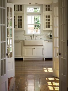 nice white cabinets to ceiling, farmhouse/apron sink, decorative glass