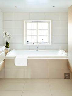 DYRKER LYSET: Beboerne ønsket å utnytte dagslyset mest mulig. Derfor er badekaret plassert ved vinduet, og gardinene er borte. Alle flater, med unntak av gulvet i dusjhjørnet, er lyse og lysreflekterende. De sandfargede gulvflisene og de hvite veggflisene er fra Flishuset. Badekaret er fra Duravit.
