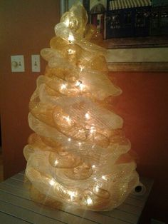 Deco mesh tree made with a tomato cage wired with lights, gold mesh and two tone gold/cream mesh....