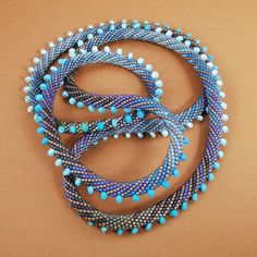 """Claire Kahn  Cylindrical Miyuki Glass Beads with Shaded Turquoise Rondelles, 42"""" Long by 0.5"""" in Diameter"""