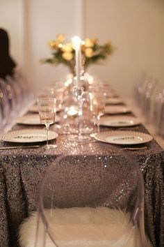 Holiday party, place settings, gold, silver, glittery, clear cups with gold polkadots, silver sequins linens, faux fur on clear ghost acrylic chair, gold silverware, gold serve ware, candles. Holiday tables. how to set up a dining table. thymes. veuve clicquot Rich Campagne