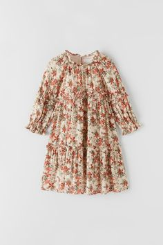 Ruffled Round Neck Dress With Long Sleeves. Back Button Closure. Gathered Detail With Floral Print And Sparkly Trim.
