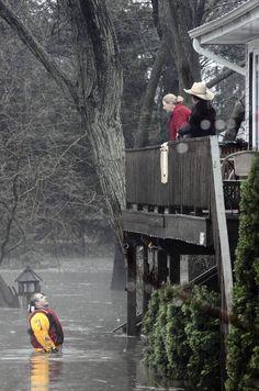 A rescuer talks to a couple at their flooded home in Lisle #poisonedweather — Antonio Perez, Chicago Tribune, April 18, 2013