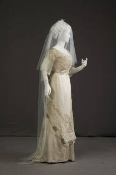 1911 Wedding dress in off-white Silk satin. Bodice has lace over-layer with a low, rounded neckline. C-shaped back with pearl beading and rhinestone medallions at each side. Rhinestone buckles at shoulders. Bow-shaped pearl decorations at front and upper arms, with strands of pearls at back and skirt. Three-quarter lace sleeves. Skirt has net over-layer with a large bow of pearls embroidered at front.  Purchased at Marshall Field & Co., Chicago.
