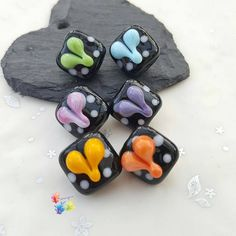 Lampwork Glass Beads Rainbow Polka Squares Per Bead Colour your world & be happy! Who doesn't love a rainbow? These cute beads are set on a black base, decorated with white polka dots and a raised heart on each side. #glitteringprizeglass #rainbow #lampwork #handmade #jewelrydesign #jewellerydesign #heart #polkadots