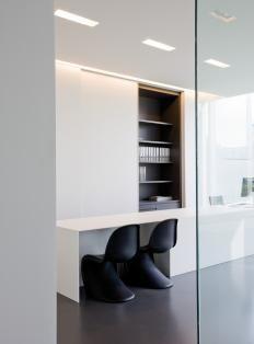 white cabinets black interior shelving and sleek contemporary desk - black Panton chairs - office/studio